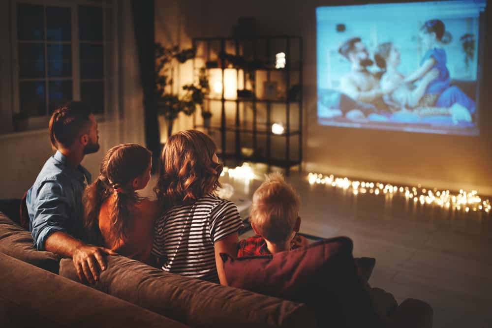 A family of four watching a movie together.
