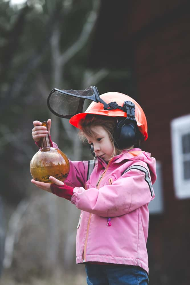 A girl wearing safety gear doing experiments at the backyard.
