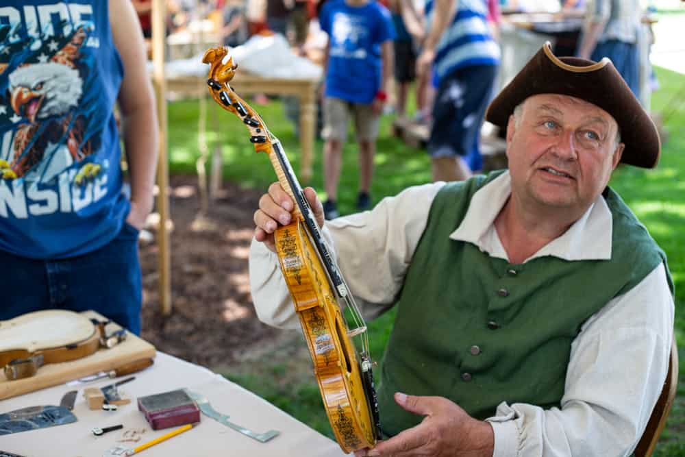 A man holding up a hardanger fiddle violin.