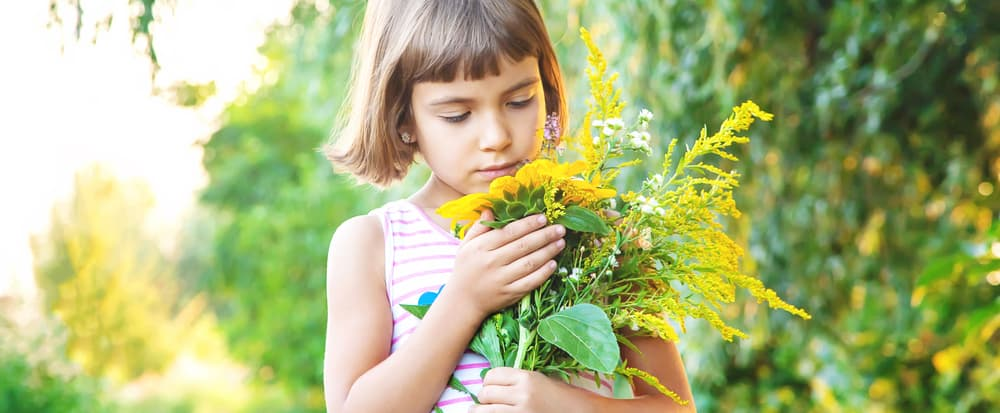 A close look at a girl holding a bouquet of wildflowers.