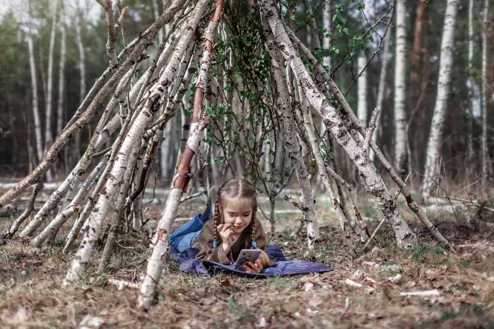 A girl in a makeshift stick house teepee.