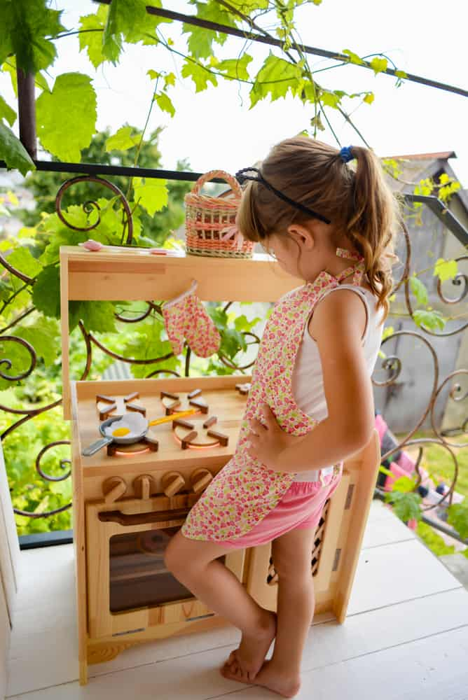 A girl playing with a kitchen set toy.