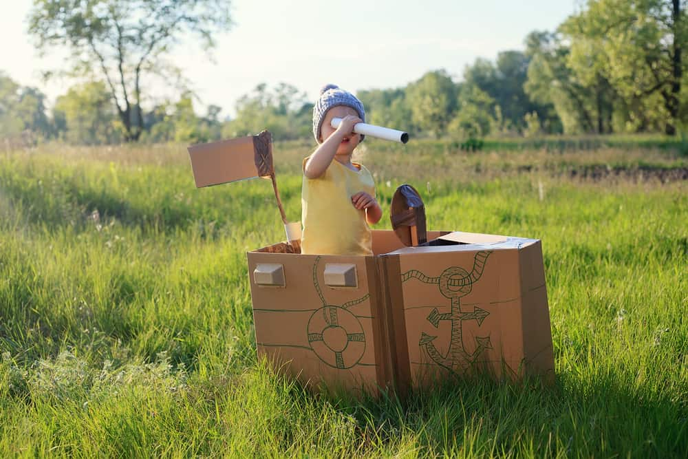 A kid playing on a makeshift carton boat.