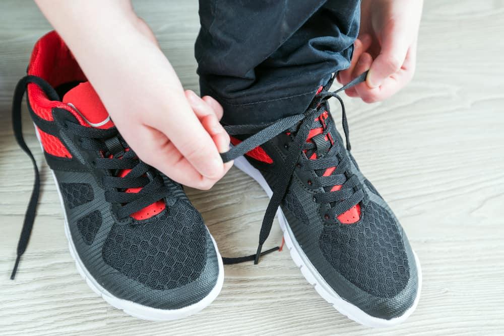 A close look at a boy lacing his sports shoes.