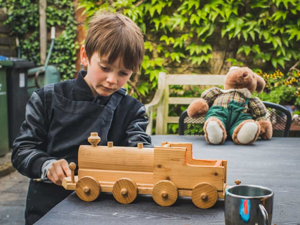 A boy playing with a recycled wooden toy truck.