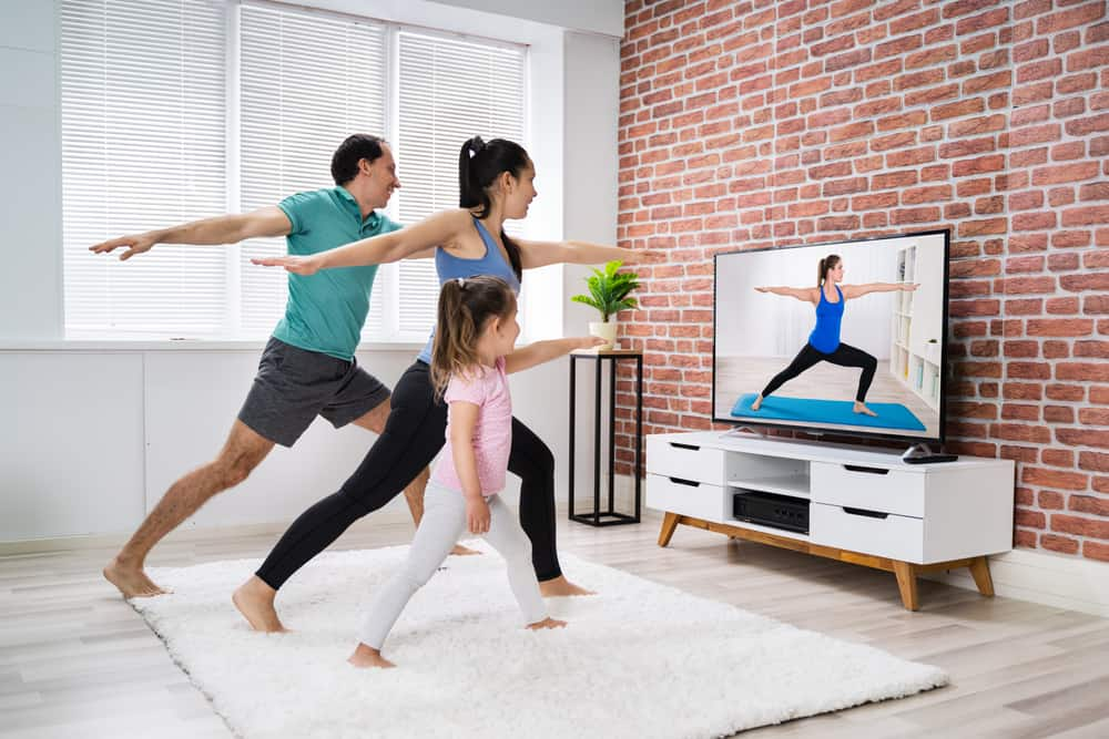 A family doing yoga together in front of the TV.