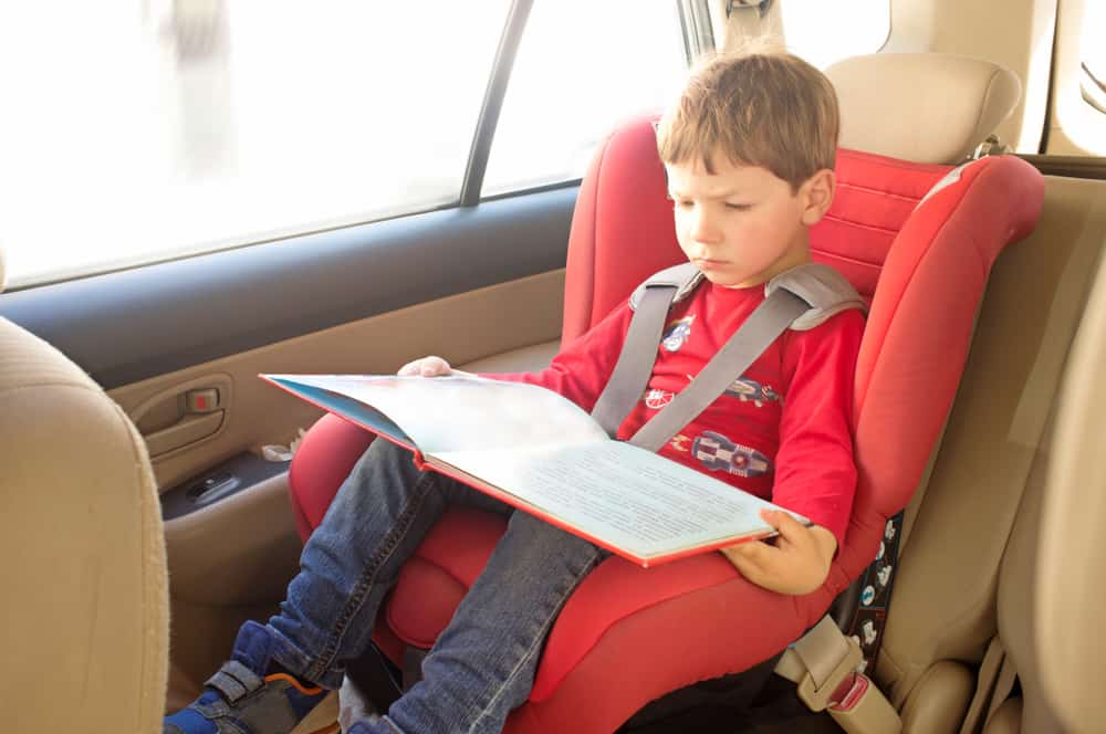 A kid reading a book inside the car.