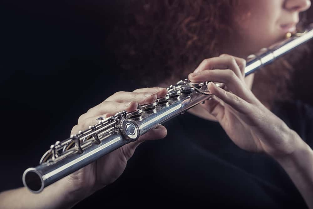This is a close look at a woman playing the flute.
