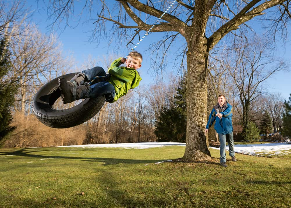 A father and son playing on the tire swing.