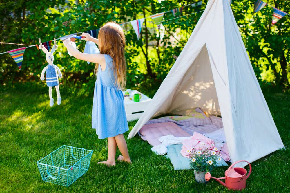 A girl playing with her teepee in the backyard.