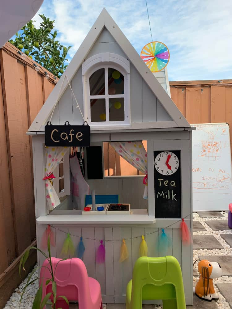 A makeshift wooden playhouse with cafe.