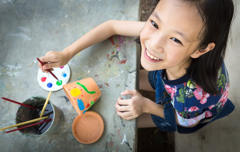 Girl painting the flower pots.