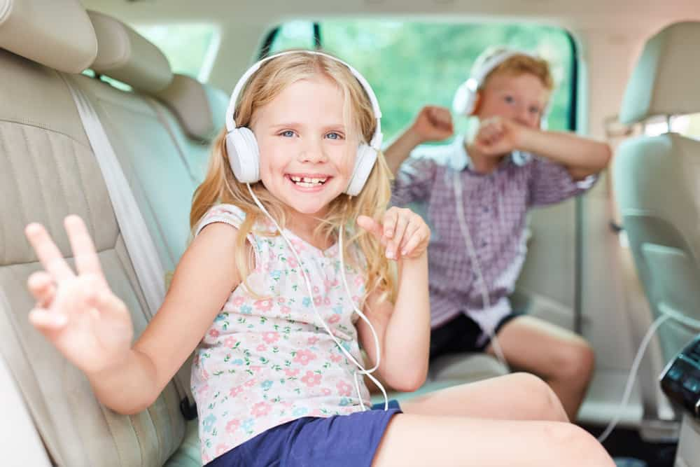 children listening to music with their headphones in the car.