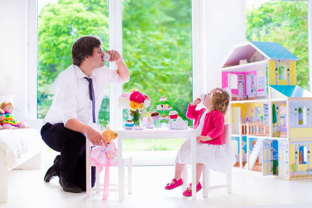 A father and a daughter having a play tea party.