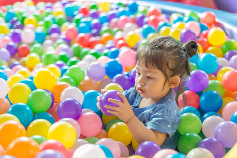 A girl playing in the ball pit.