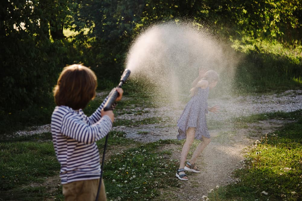 Kids playing with a water sprinkler.