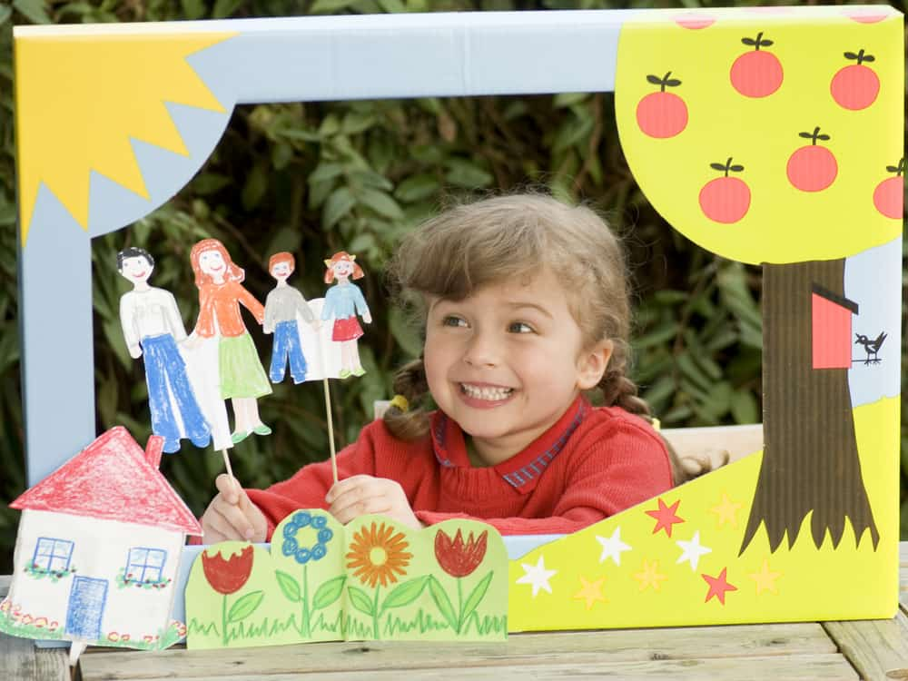 Girl playing with a puppet theater.