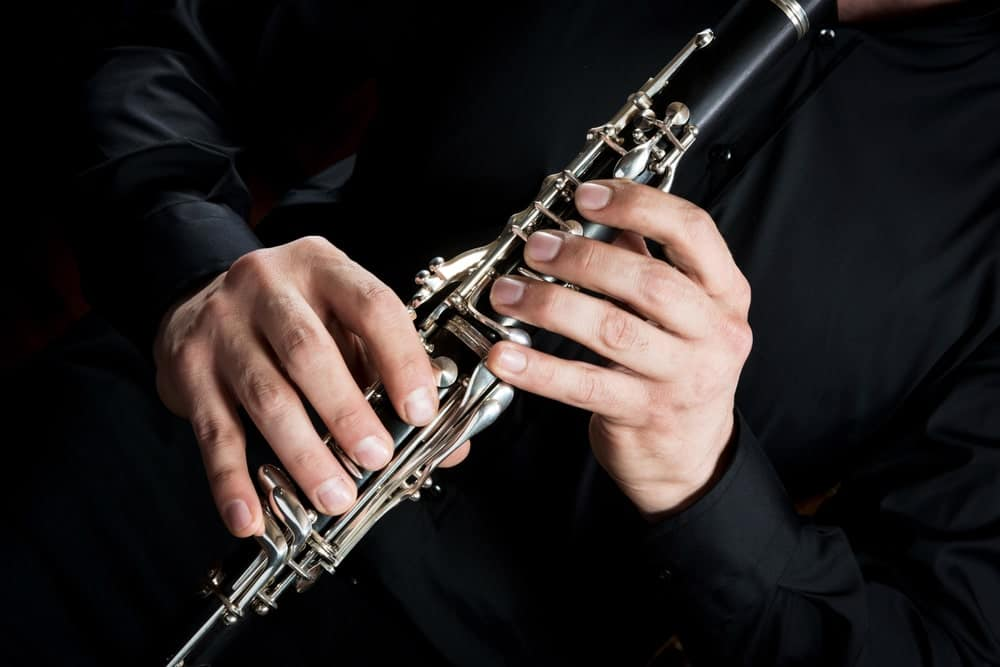 Cropped image of a musician's hands on a clarinet.