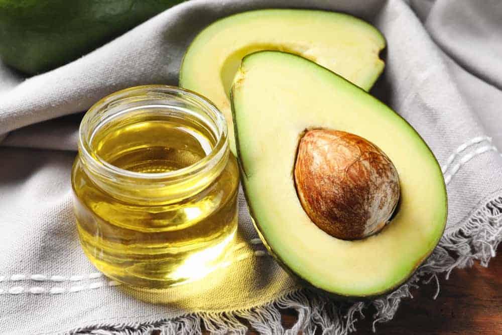 A small jar of avocado oil beside sliced avocados on a gray cloth.