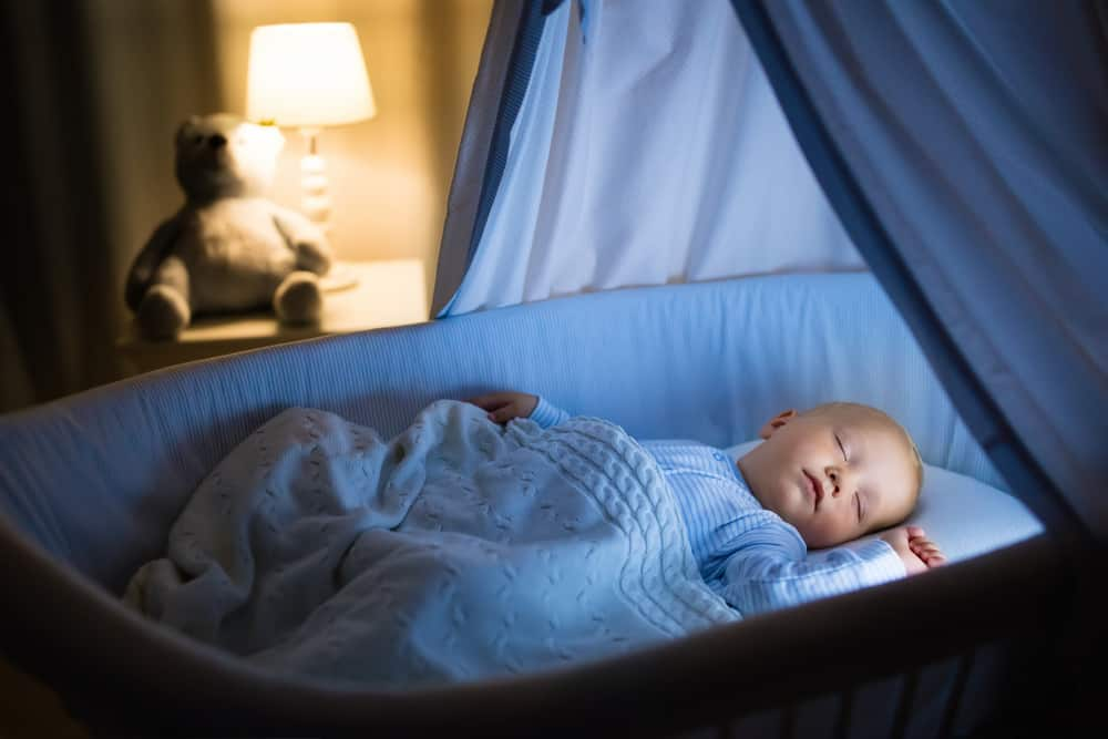 Baby boy sleeping in blue bassinet with canopy.