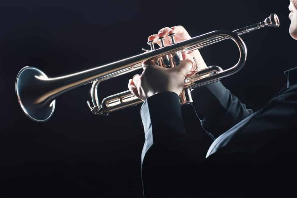 Musician playing a trumpet against black background.