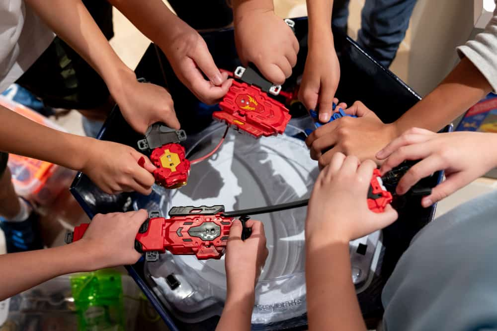 Kids holding their beyblade launcher over a beyblade stadium.