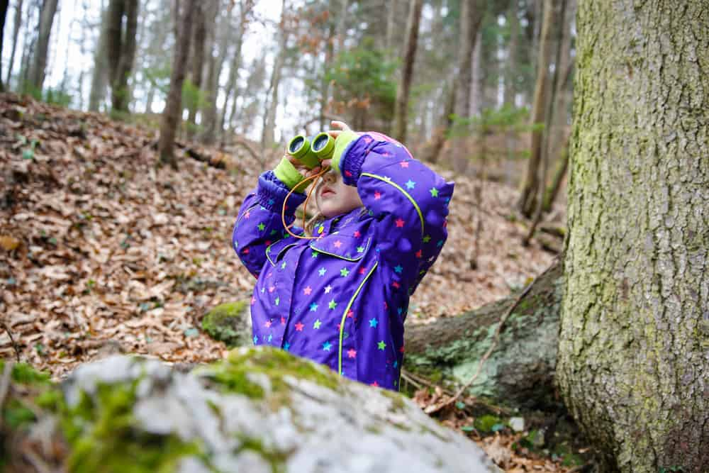 Girl looking through the binoculars in the forest.