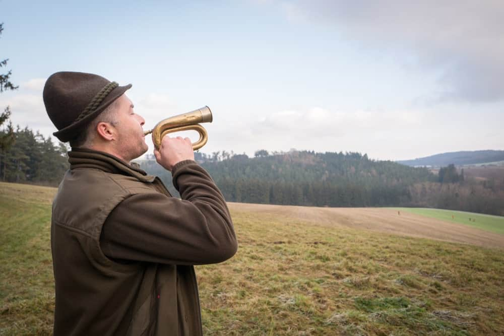 Old man using a bugle at a farm.