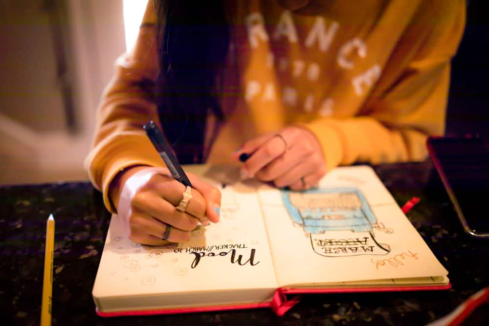 Young girl writing on her bullet journal.