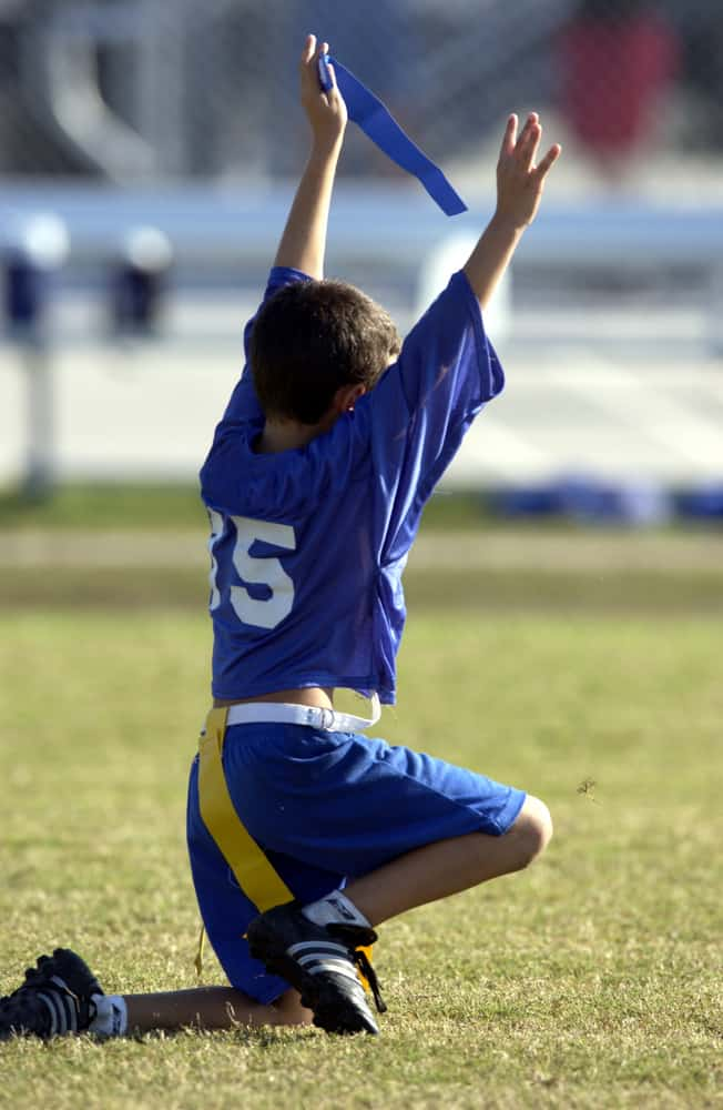 Boy in blue jersey playing capture the flag.