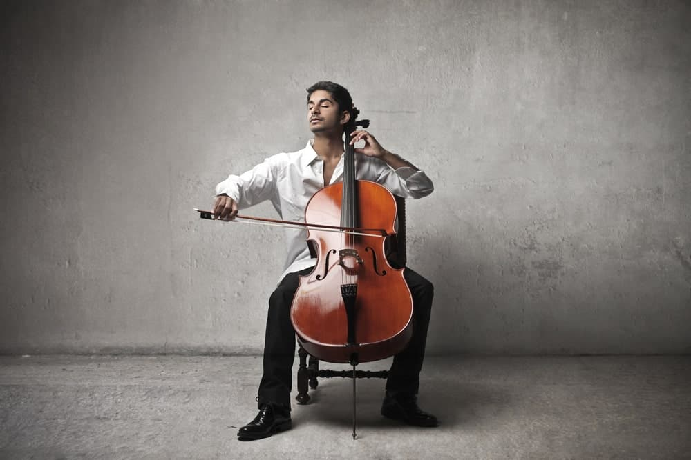 A man sits and closes his eyes playing a cello against a backdrop of gray.