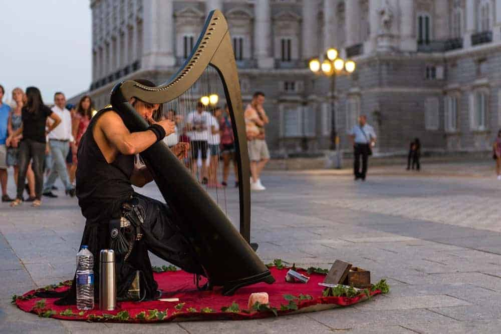 A man playing a black celtic harp at the town plaza.