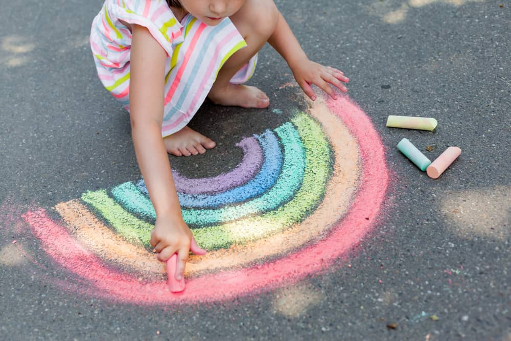Girl drawing a rainbow using colored chalks on the asphalt.