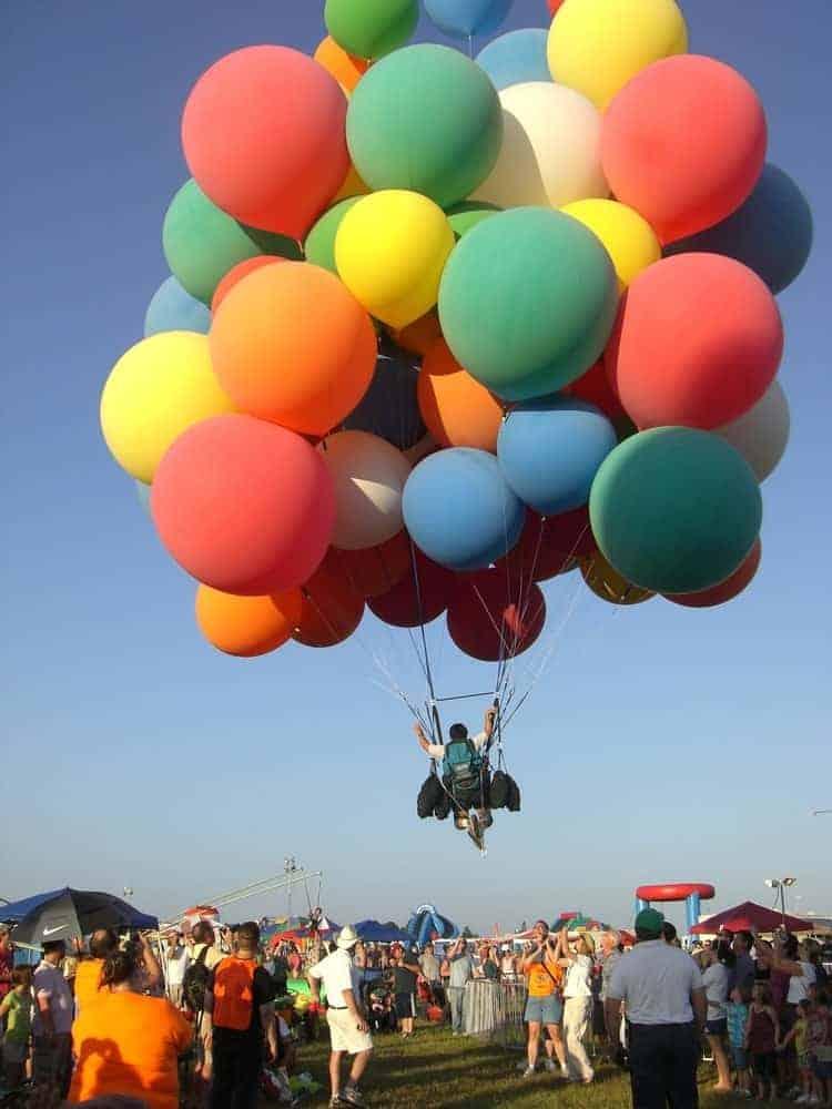 A man flies away in a cluster balloon.