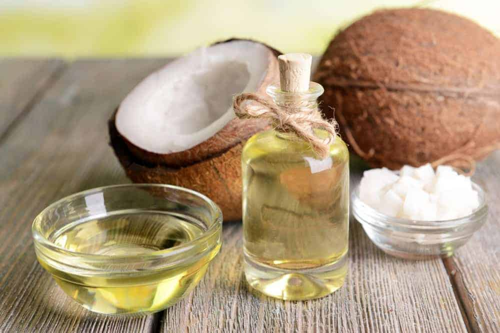 A small bottle and bowl of coconut oil beside coconuts and a bowl of coconut cubes on a wooden surface.