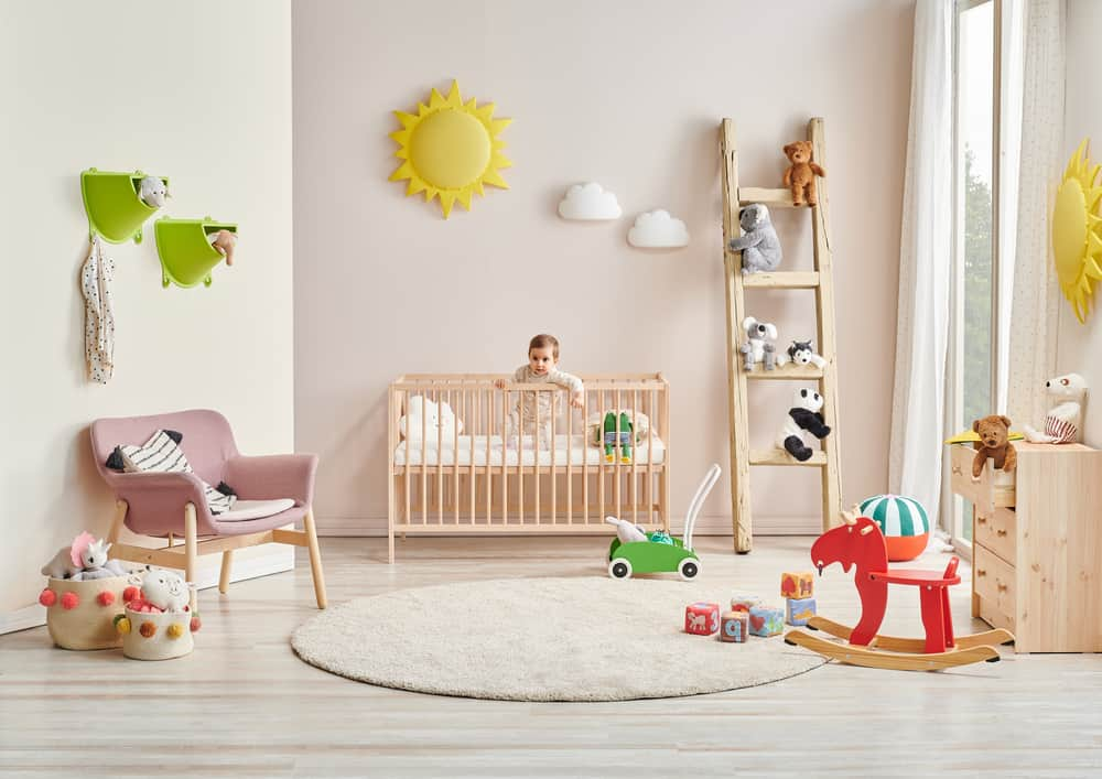 Nursery room with a cot bed, a wooden ladder, pink armchair, and a rocking horse.