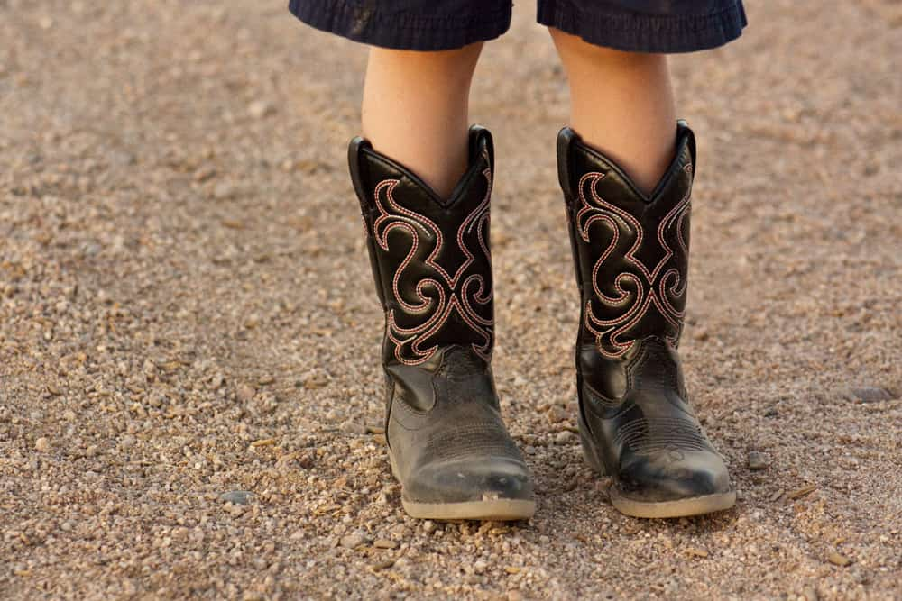 Kid wearing cowboy boots standing on the gravel.