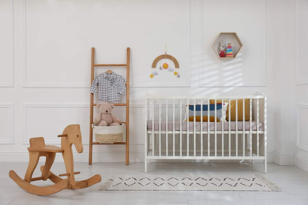 Nursery room with a wooden ladder, a rocking horse, and a white crib complemented with a tasseled runner.