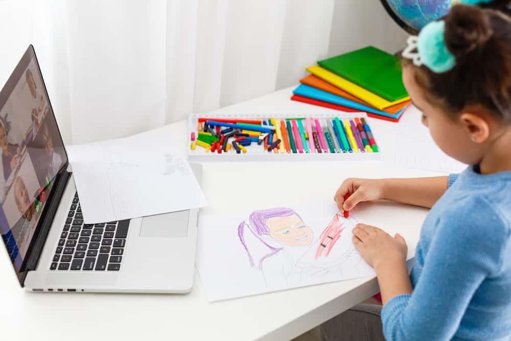 Little girl doing an activity during her online class.
