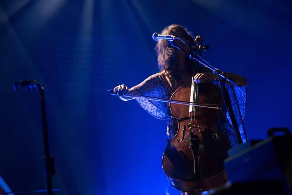 A woman plays an electric cello.