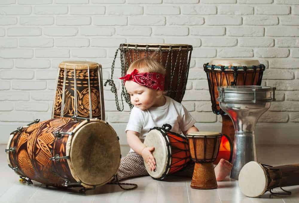 Baby playing with various types of drums.