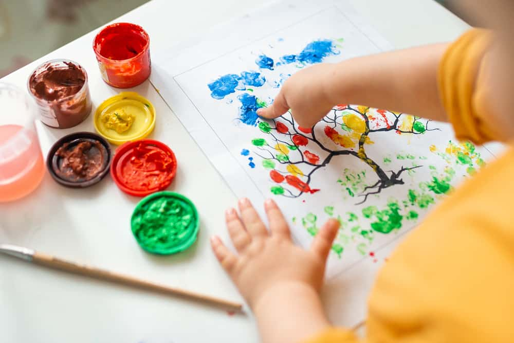 Little girl painting a tree using her fingers.