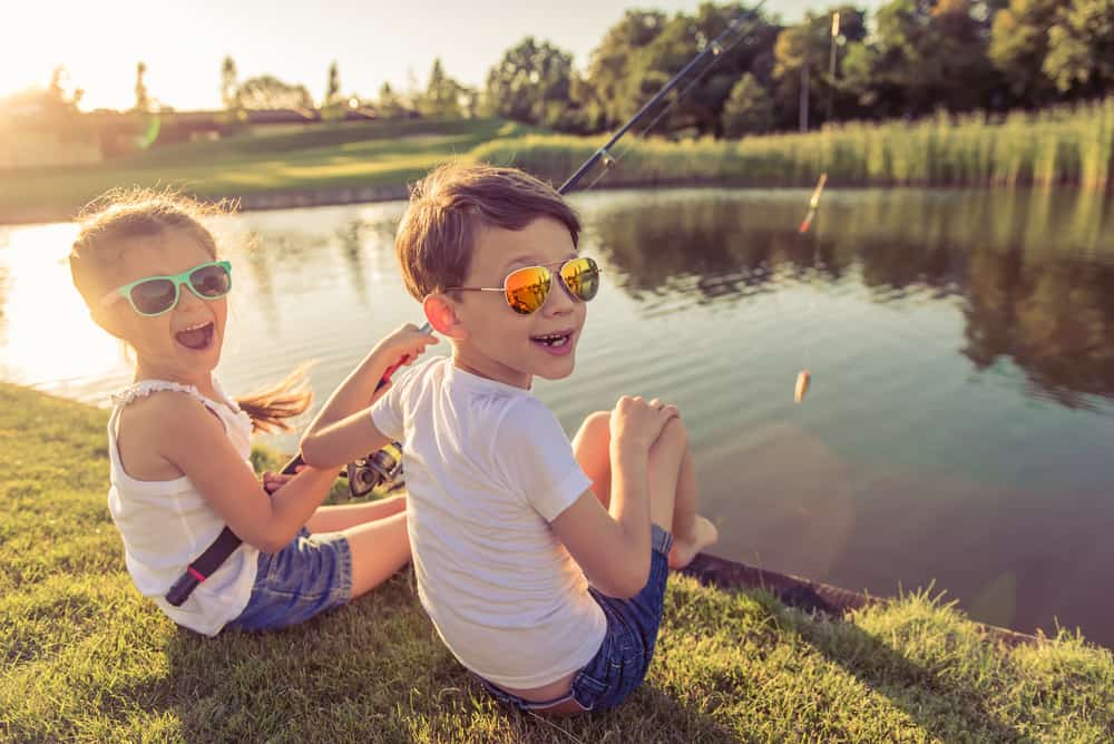 Little boy and girl in sunglasses fishing in the pond.