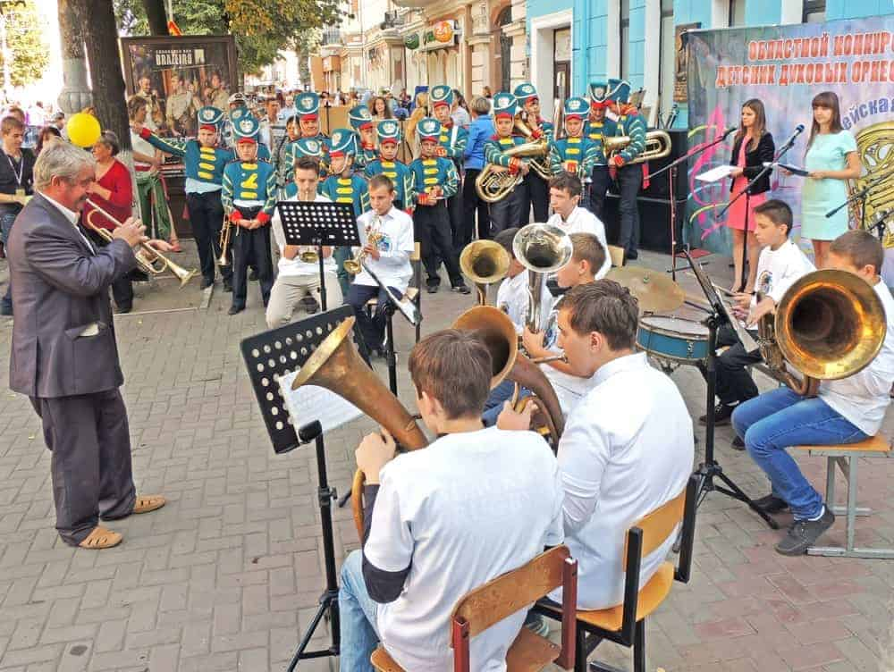 Street choir playing different musical instruments including trumpets, drums, and helicon tuba.