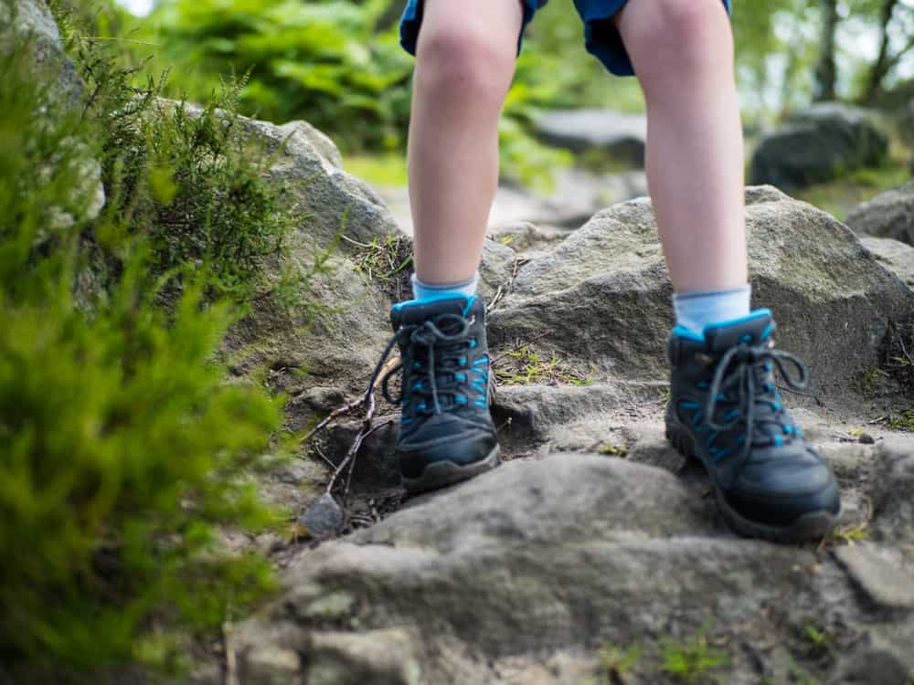 Boy in hiking boots standing over a boulder.