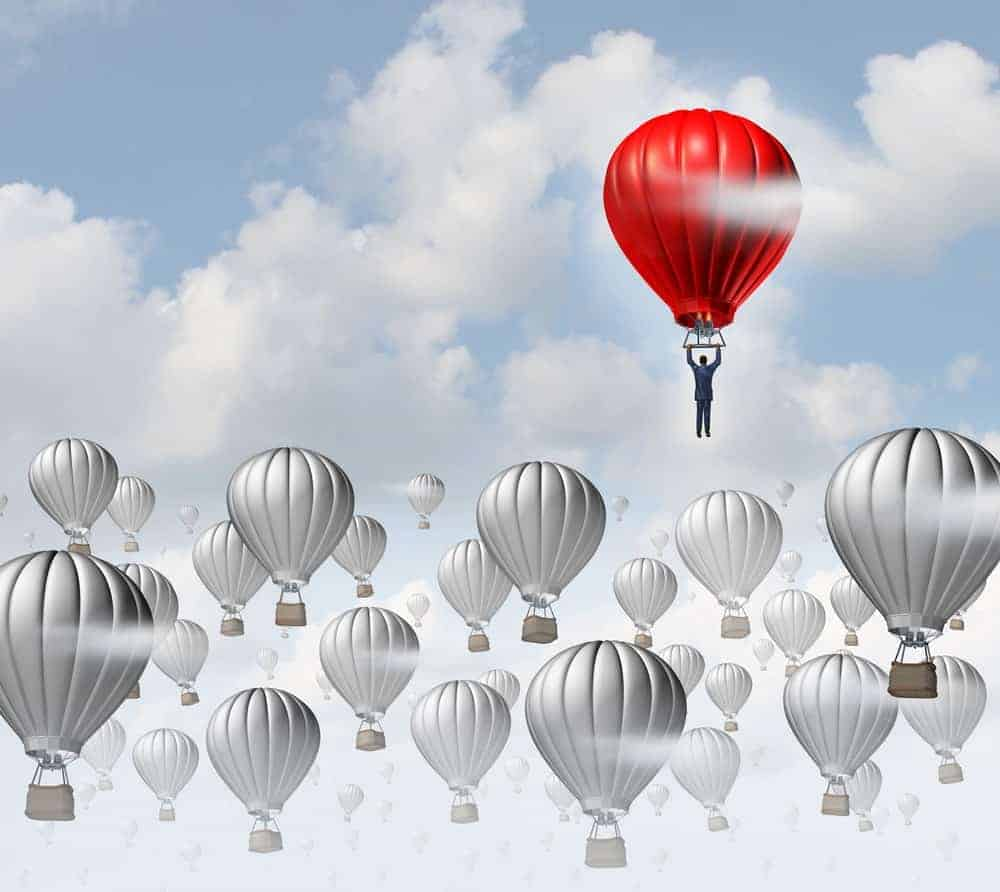 A man flies away in a red hopper balloon.