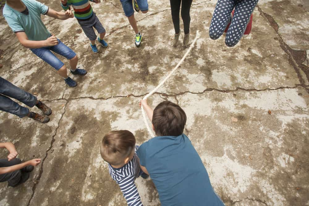 Kids playing jumping rope on the ground.