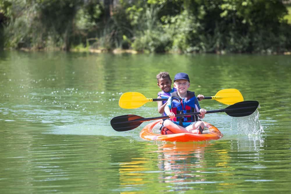 Little boys kayaking down the river.