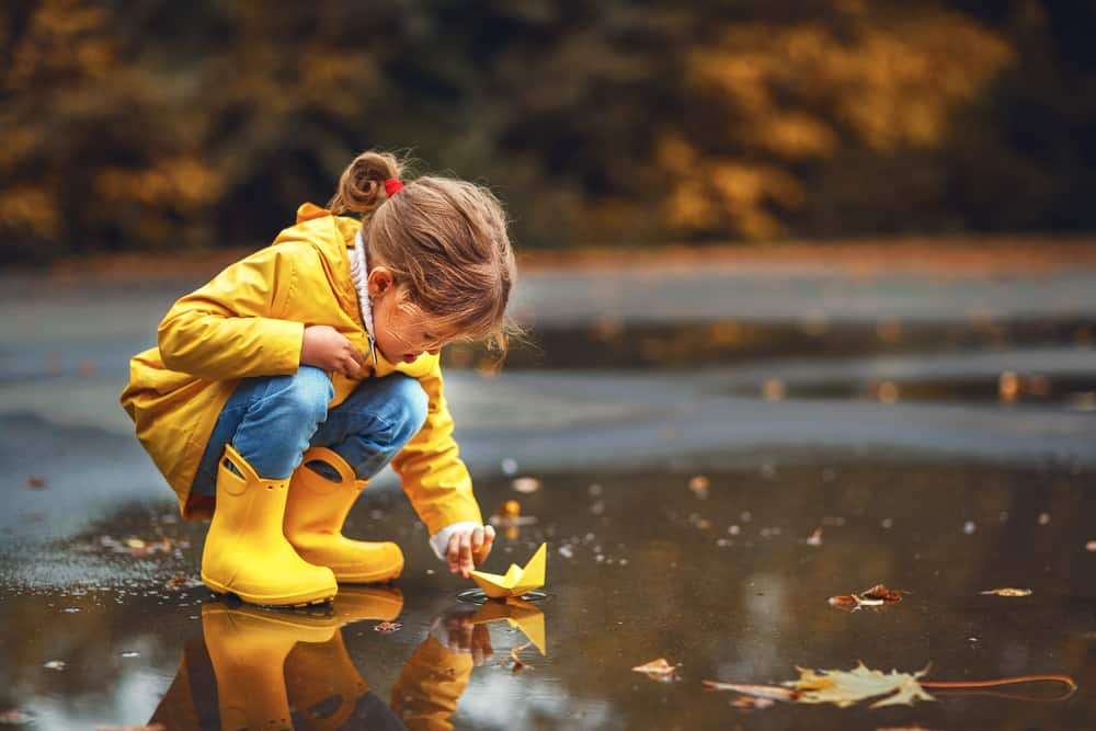 Girl wearing yellow raincoat and boots playing with paper boat on a puddle.