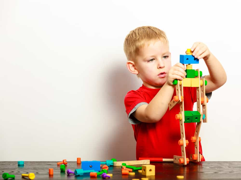 Little boy playing with colorful building blocks.